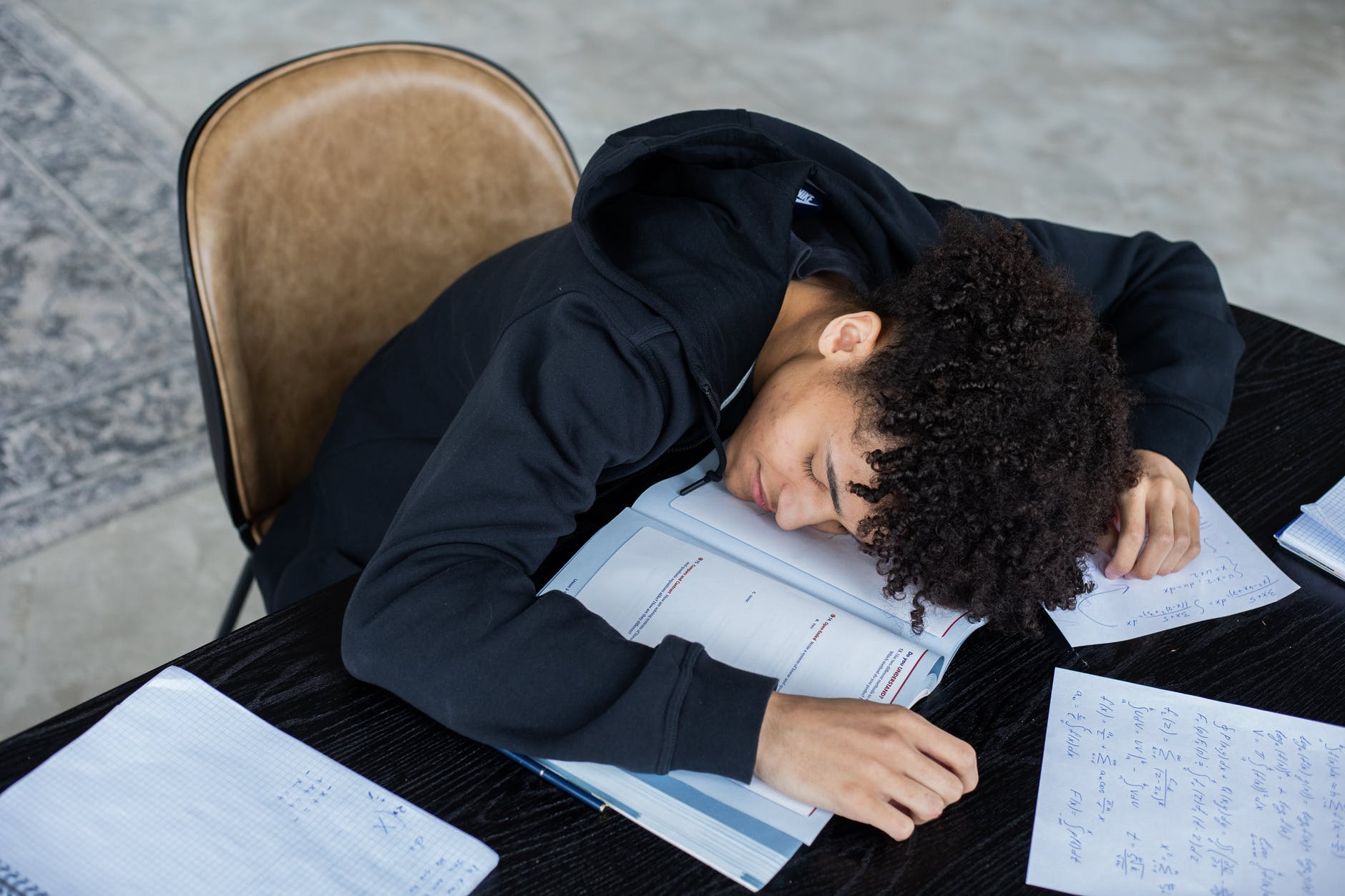 Exhausted college athlete doing school work.